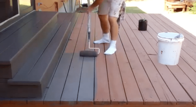 man staining his deck