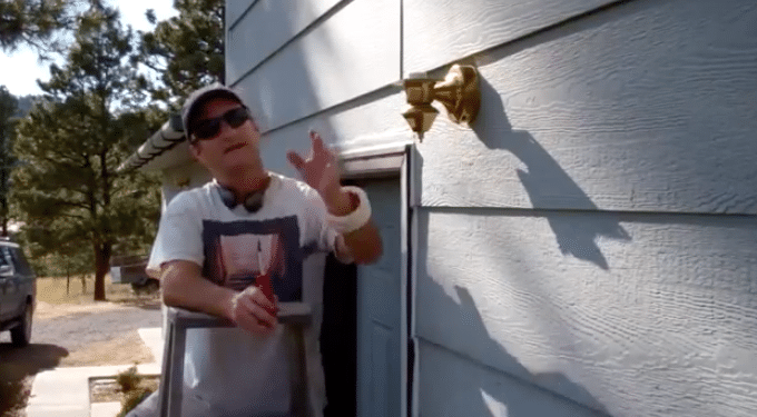 man removing light fixture from home